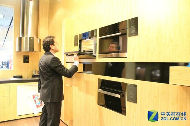 一位与会者好奇的打开老板烤箱,仔细观察内部结构。